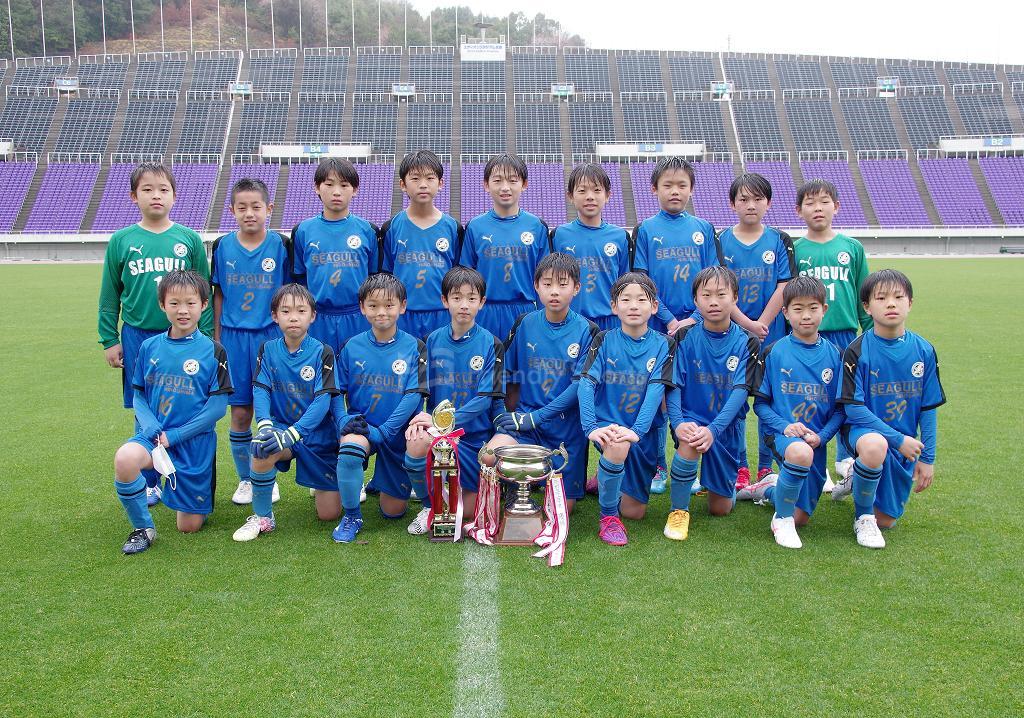 広島市スポ少 県外招待 大雨の中、シーガルが優勝カップを手にする
